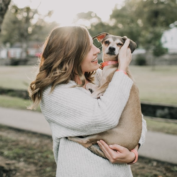 Owner carrying her pet in her arms